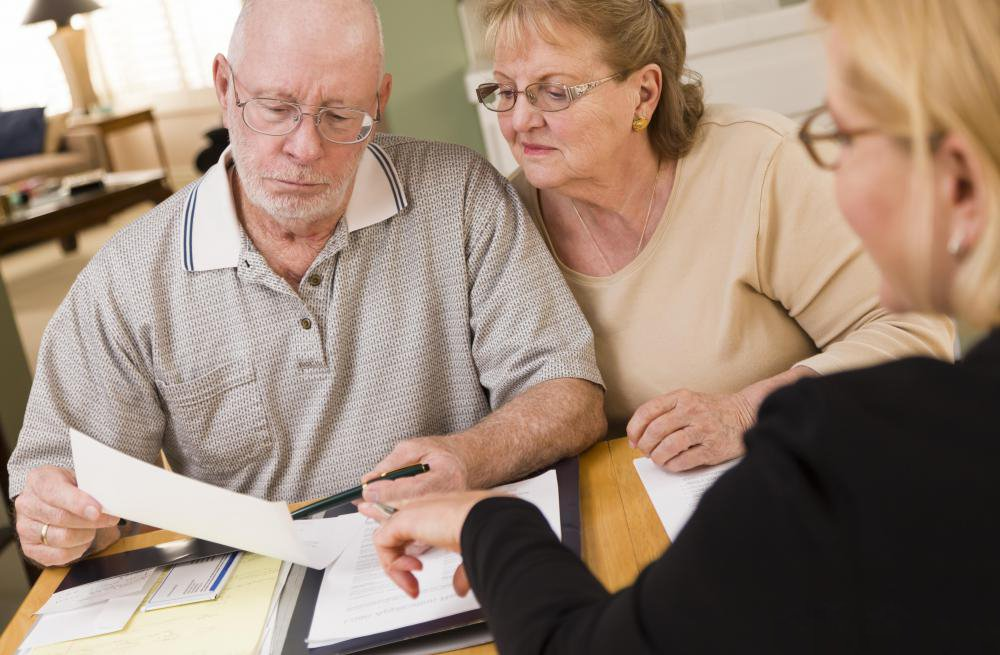 senior-couple-reviewing-papers-with-professional